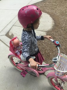 child riding bike with baby strapped into seat over back wheel