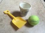 Yellow plastic shovel, empty yogurt cup, and used tennis ball