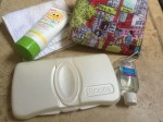 Sunscreen, portable diaper wipes case, reusable bag, washcloth, and hand sanitizer collage