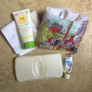 Sunscreen, wash cloth, plastic wipes case, hand sanitizer, and reusable bag on floor