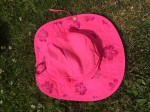 Sun Protection Zone bright pink wide brim sun hat with chin strap and purple flower designs that appear in sunshine