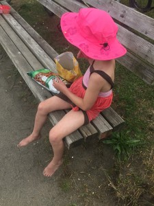 Girl wearing pink sun hat eating snacks on beach