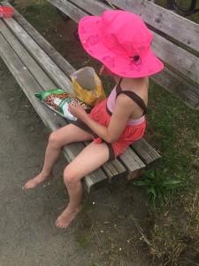 Girl wearing pink sun hat eating snacks on beach