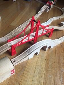 Brio red suspension bridge in track layout on wooden floor