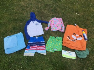 Swim suits and trunks and sunscreen and googles and towels wipes and plastic bag on grass