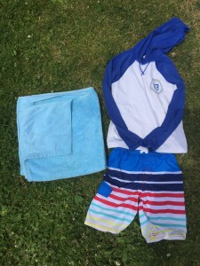 Towel, swim shirt, and swim trunks on grass