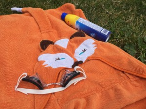 Hooded orange fox towel, spray sunscreen, and googles