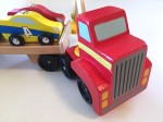 Melissa and Doug wooden car loader with red tractor trailer flatbed and four striped cars with numbers