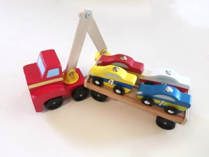 Melissa and Doug wooden car loaded with four car loaded onto flatbed