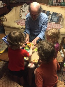 Kids and grown up choosing cards to play Parker Brothers Avalanche marble game
