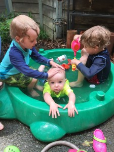 Three kids in turtle sand box from Little Tikes filled with water