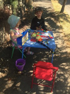 Kids with table set up on sidewalk selling homemade crafts