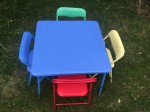 Kids blue folding table set up with folding chairs in blue yellow green and red
