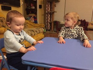 Toddler and preschooler sitting at blue kids folding table