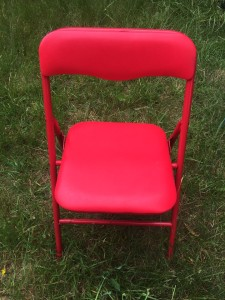 Kids folding chair in red set up on grass