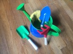 Toysmith kids small gardening tools set with blue watering can, green shovel, blue trowel, red rake, and yellow gloves