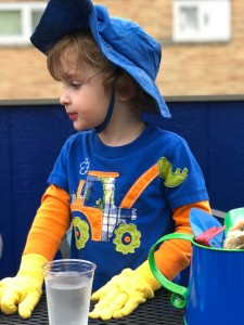 Child wearing yellow garden gloves at table