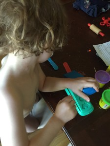 Child playing with Play-Doh fun factory on table