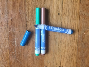 Crayola window markers in green, brown, and blue laying on wooden floor
