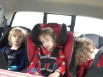 Three kids in car seats in one row two kids asleep