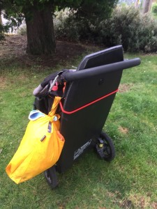 Boogie board strapped onto back of Bob motion stroller with Toogli hook visible holding yellow bag