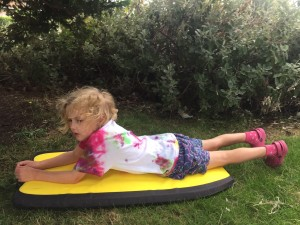 Six year old laying on yellow boogie board in grass by bushes at park