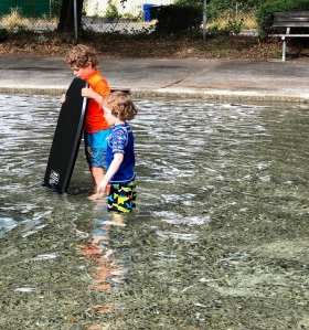 Two kids holding boogie body board in wading pool