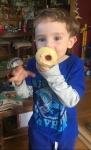 Child holding cupcake in front of his mouth