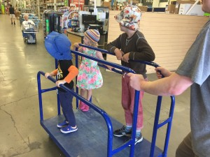 Three kids riding on blue flat car in home improvement store