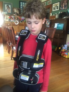 Child wearing ride safer harness inside house