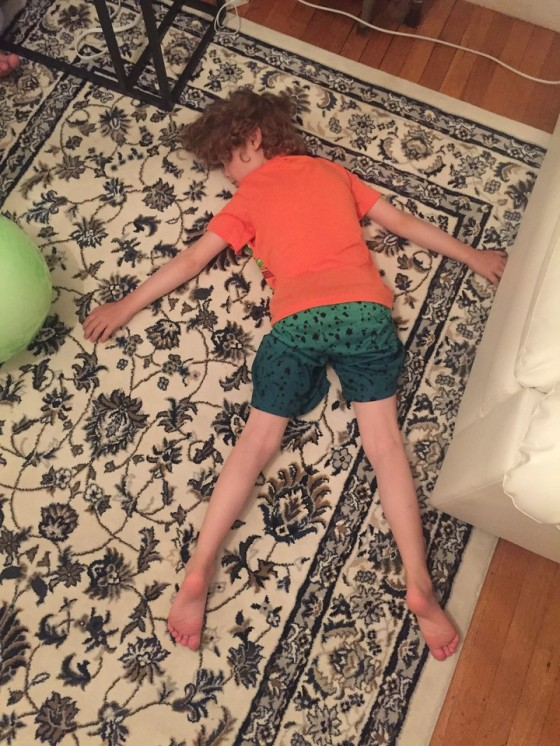 Kid passed out flat on floor on top of rug