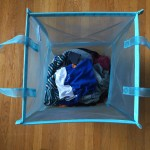 Blue folding mesh tote laundry hamper bin with handles and laundry inside