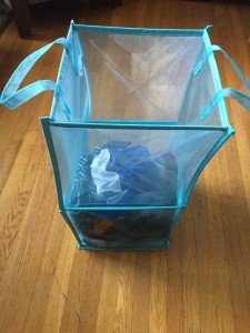 Blue mesh laundry tote bin with clothes partially full
