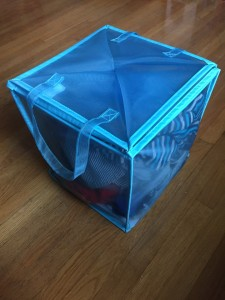 Mesh double cube folded partially to half the size with laundry inside