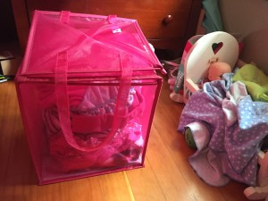 Pink folding laundry hamper half folded with laundry inside