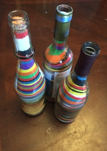 Three wine bottles filled with layers of different colored sand by young children