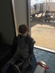 Child eating burrito at airport window waiting to board
