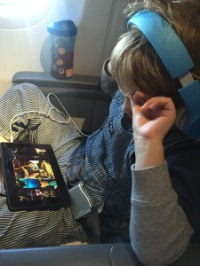 Child wearing headphone watching screen on airplane