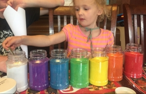 Girl using spoon to scoop up colored sand from jars