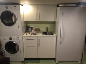 Frigidaire stacking washer and dryer installed in basement laundry area