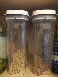 OXO Good Grips medium airtight POP cereal dispensers side by side in cabinet with cereal partially filled