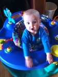 Infant inside Evenflo Exersaucer in blue and green