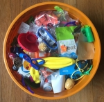 Large orange bowl filled with small plastic toys, stickers, sunglasses, balloons, and more for trick or treating