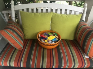 Orange Halloween bowl sitting on white front porch swing striped cushions