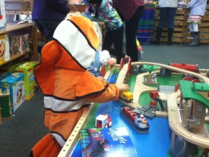 Child wearing clownfish Nemo hooded costume playing at train table