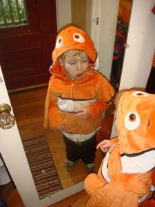 Child looking in mirror while wearing Disney Nemo clownfish costume hooded