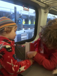 Preschooler and child playing with Super Wings New York playset on board train