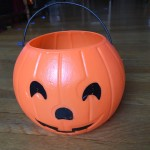 Orange plastic pumpkin with black jack o lantern face and handle for collecting Halloween candy