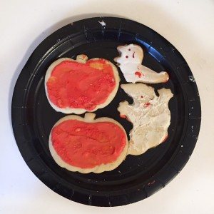 Halloween sugar cookies pumpkins with orange frosting, white ghost, half eaten cat