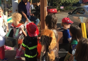 Kids collecting candy during Halloween trick or treat from local business